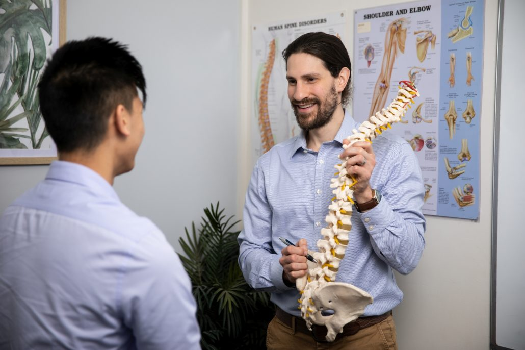 Dr Domenic Simeoni Physio using spine model to explain low back pain to client