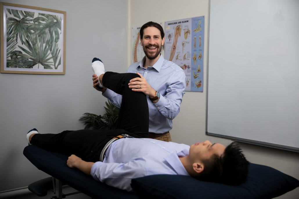 Physio Domenic Simeoni assessing the leg and achilles tendon