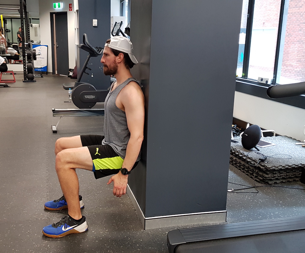 physio performing wall sit for strength - how to avoid knee pain