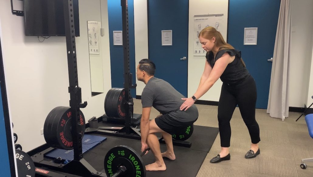 Physio Brittany Taylor observing and correcting exercise rehab session